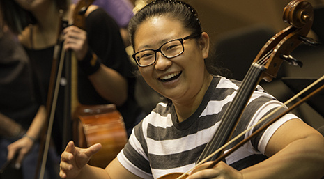 smiling cello student performing