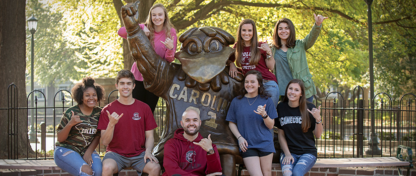 Group of students around mascot statue