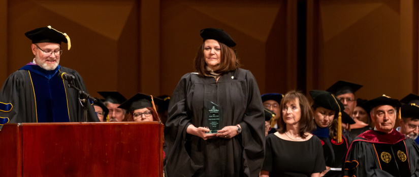A professor accepting an excellence in teaching award from the dean