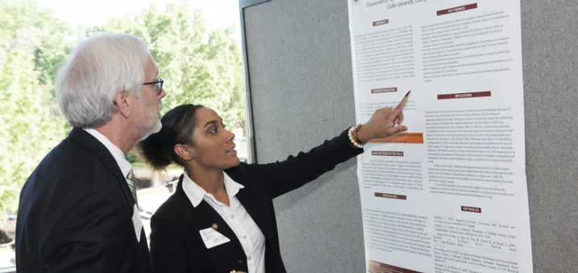 Two individuals discussing an informational poster