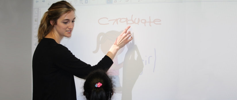 Student demonstrating something on a white board to a child