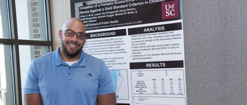 Student posing in front of research poster