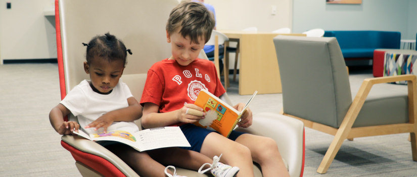Two kids seated reading books
