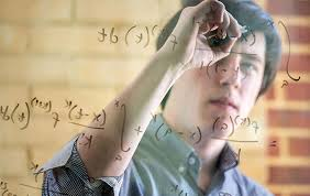 Man writing math equations on a piece of glass