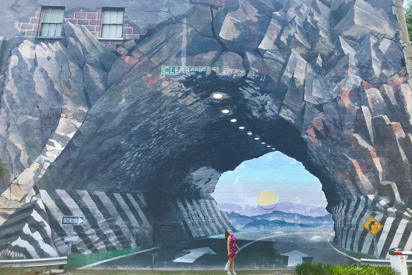 Tunnel Vision mural by the artist Blue Sky with Mia Grimm standing in for perspective.