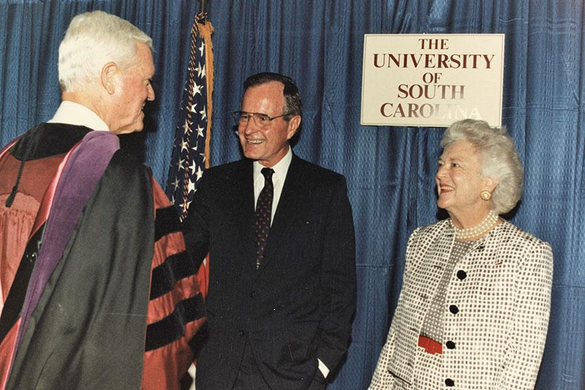 President George H.W. Bush and Barbara Bush shake hands with Fritz Hollings in front of a UofSC sign.
