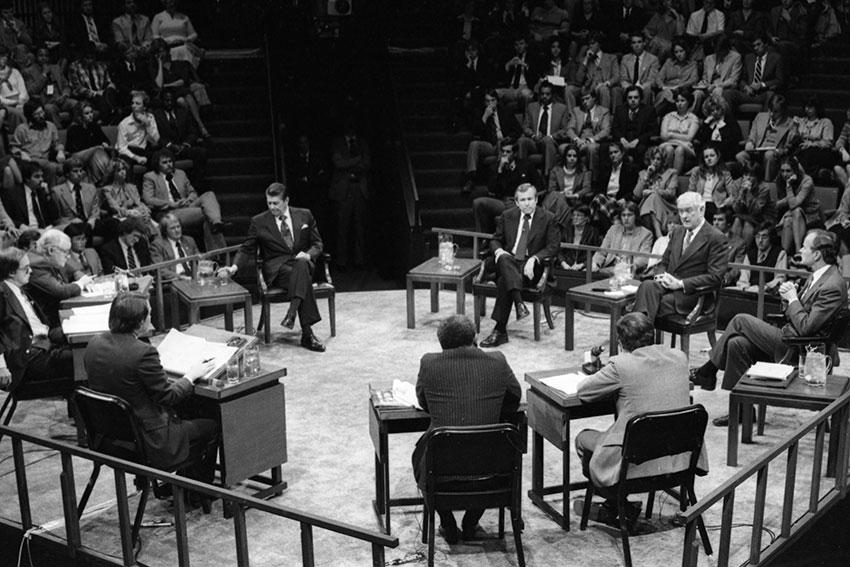 1980 presidential debate in Longstreet Theater featuring Ronald Reagan and George H.W. Bush, among others sitting in a circle on stage.