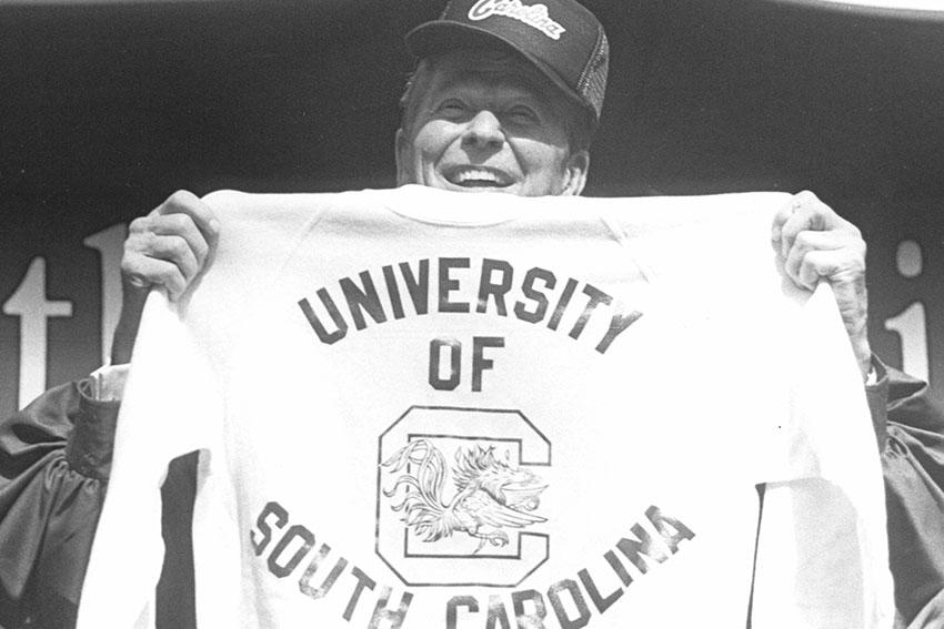 Ronald Reagan displays a UofSC hat and sweatshirt.