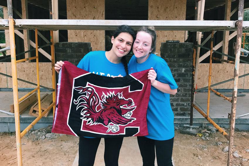 Jaclyn Altizio and Abbie Fahey holding up UofSC flag in front of construction.