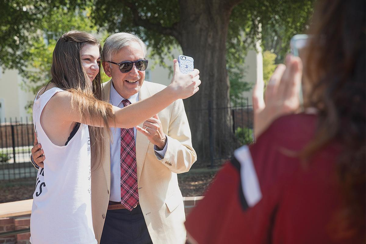 Harris Pastides taking a selfie with a student