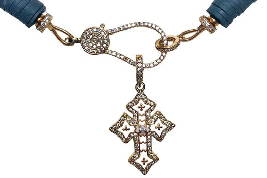 a piece of jewelry that consists of silver cross on a loop connected to a necklace