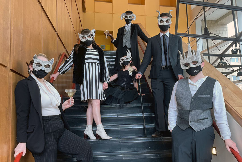 Six people wearing masks stand and sit on a stairwell.