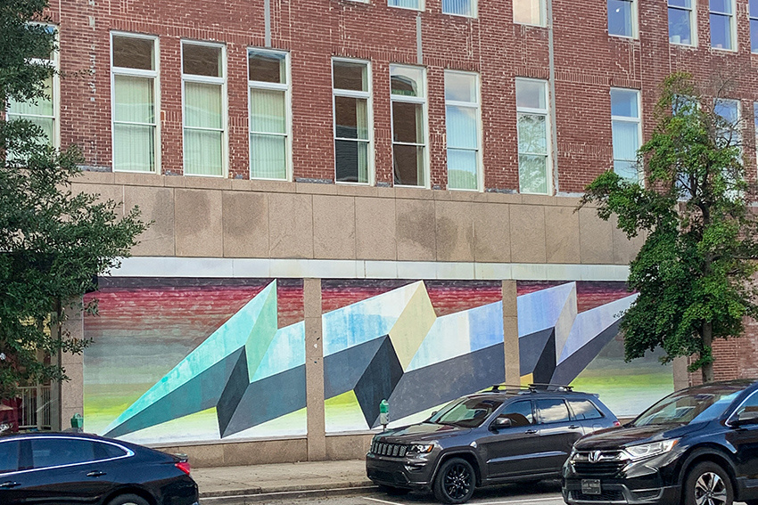 Mural on the side of a building depicts geometric shapes in greens, yellows and blues.