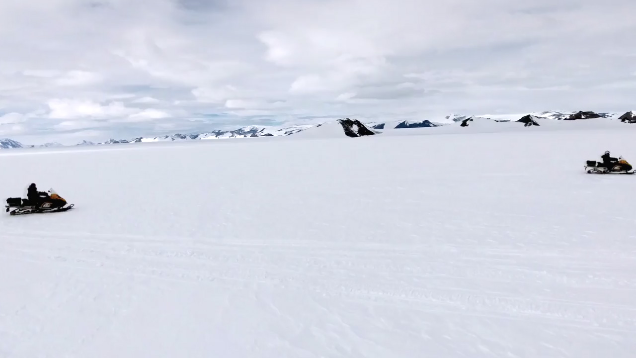 People riding in skidoos across the snow in Antarctica