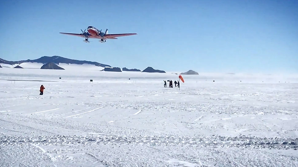 An airplane takes off in Antarctica as people watch below