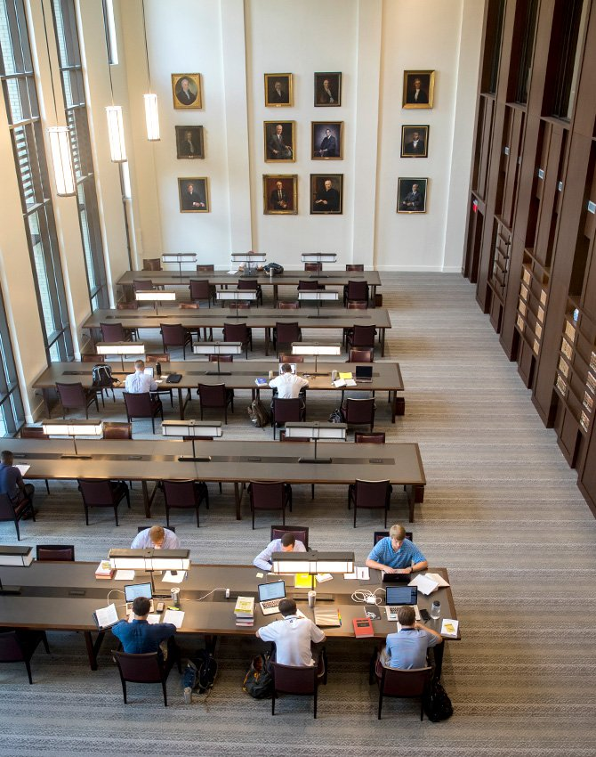 Students studying in the Coleman Karesh Reading Room with portraits haning on the wall