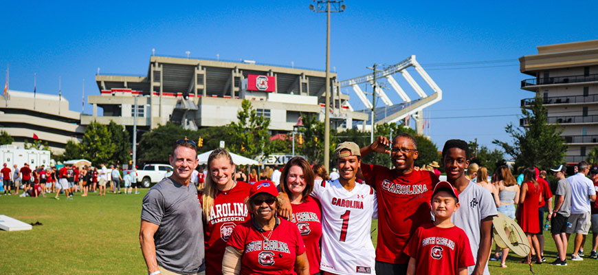 A large Gamecock family smiles brightly at the photographer while standing against the backdrop of Williams-Brice Stadium in the distance.