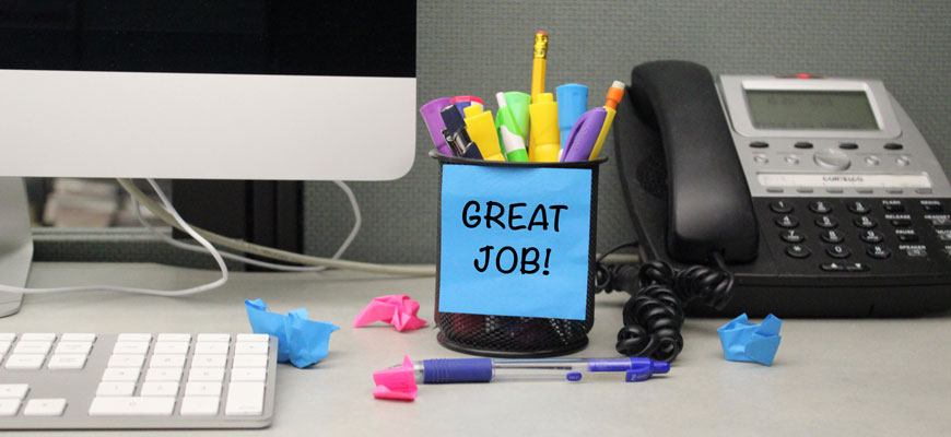 "cup of pens on a desk with a phone and computer with post-it note that reads ""great job"""