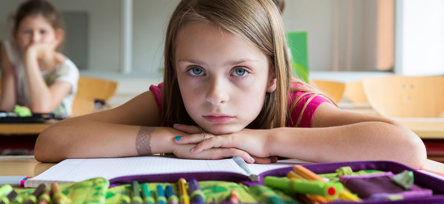 girl with chin on arms with notebook and crayons