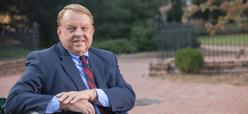 College of Arts and Sciences Dean Lacy Ford sits on a bench on the University of South Carolina campus