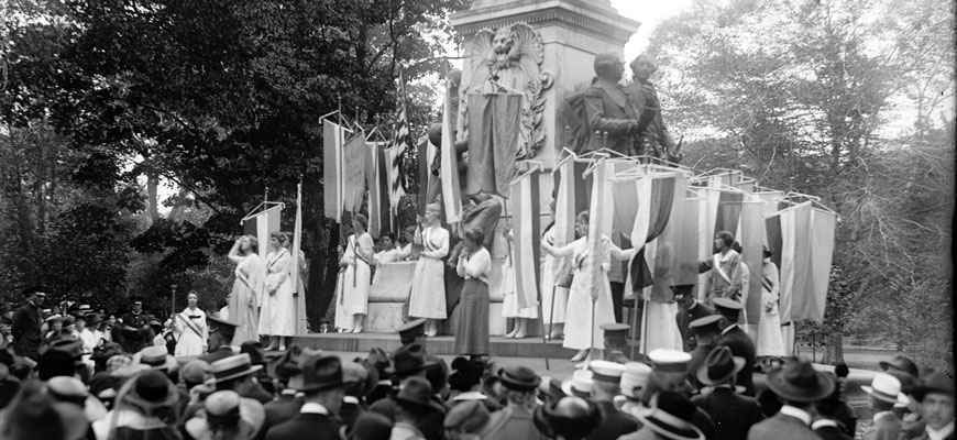 women with banners stand in front of a crowd near a monument in washington, DC, in 1918 to advocate for women's suffrage