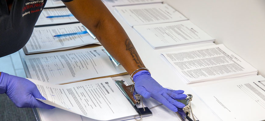 health worker handles form dealing with COVID-19 testing