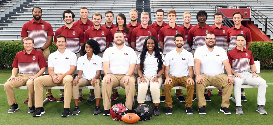 Kjahna O and Gamecock football colleagues pose for a group photo on the field