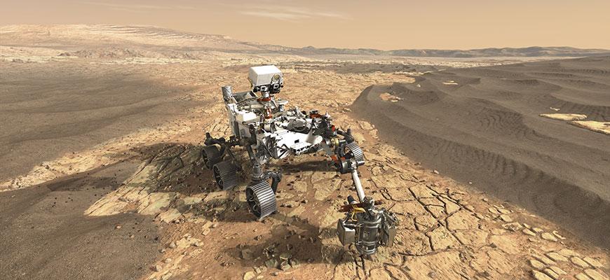 Photo illustration of a metallic, six-wheeled Mars rover on a barren dirt surface resembling Mars
