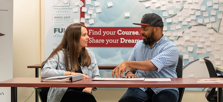 An advisor sits at a table with a student. Behind them is an environmental graphic that reads, 'Find Your Course. Share Your Dream.'