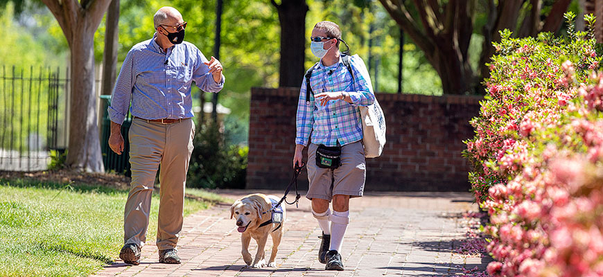 Journalist Harry Smith and Rhodes Scholar Jory Fleming walk along a brick path on the UofSC campus; flowers bloom on the right side of the photo. Fleming is walking his service dog, Daisy, as he talks with Smith.