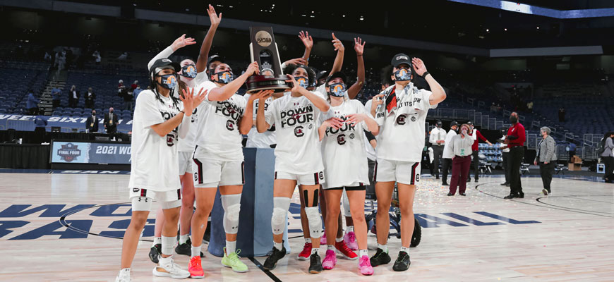 The 2021 Gamecock women's basketball team stands together on a basketball court holding an NCAA trophy as they celebrate making the Final Four.