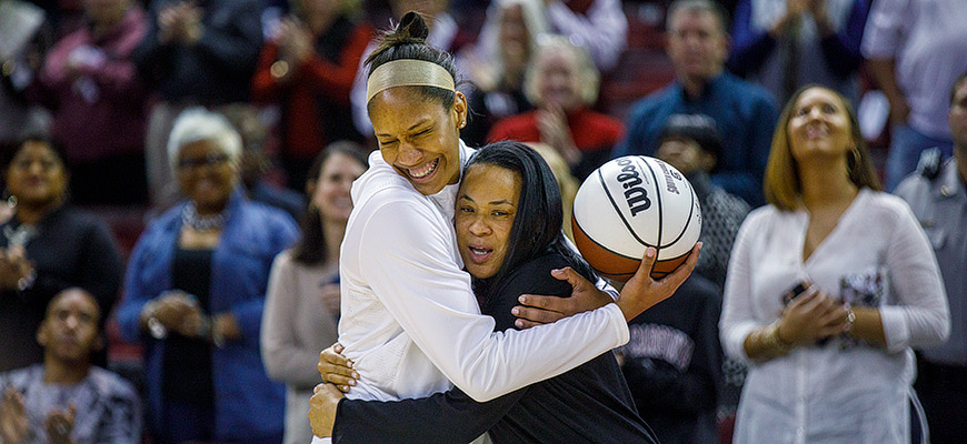 Dawn Staley and A'ja Wilson smiling and hugging on a basketball court