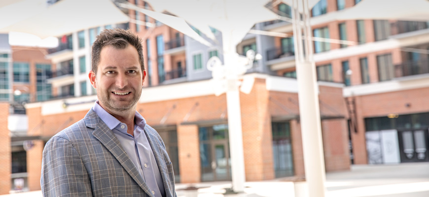 Brody Glenn stands smiling on the brick plaza of downtown Greenville development Camperdown.