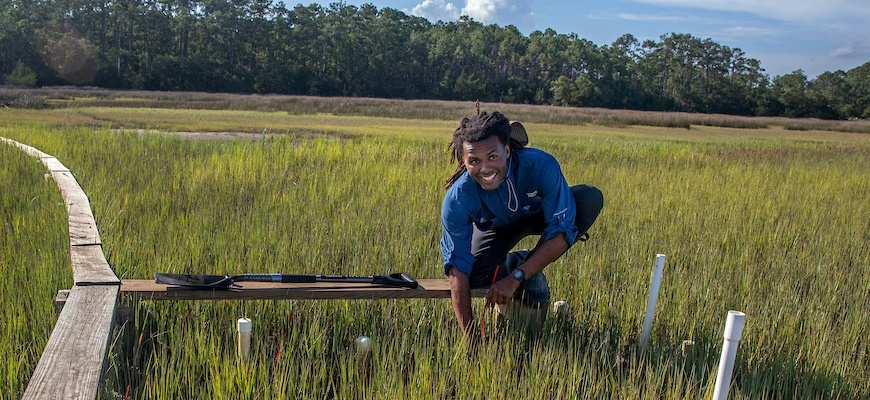 Kamari Boyd kneels in a marsh at the Baruch Institute in coastal South Carolina.