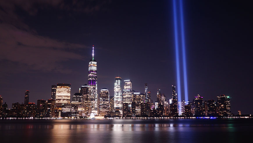 Twin beams of blue light illuminate the New York City skyline at night.