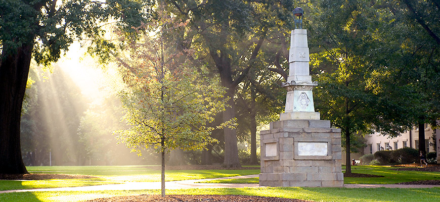 Rays of sunlight shine on grass and a tree next to the Maxcy Monument on the Horseshoe.