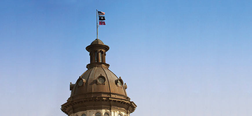 The dome of the South Carolina State House stands against a clear blue sky. Above the dome are three flags: the red, white and blue United States flag, the South Carolina state flag depicting a palmetto tree and white crescent, and a Gamecock flag depicting the Block C athletics logo.
