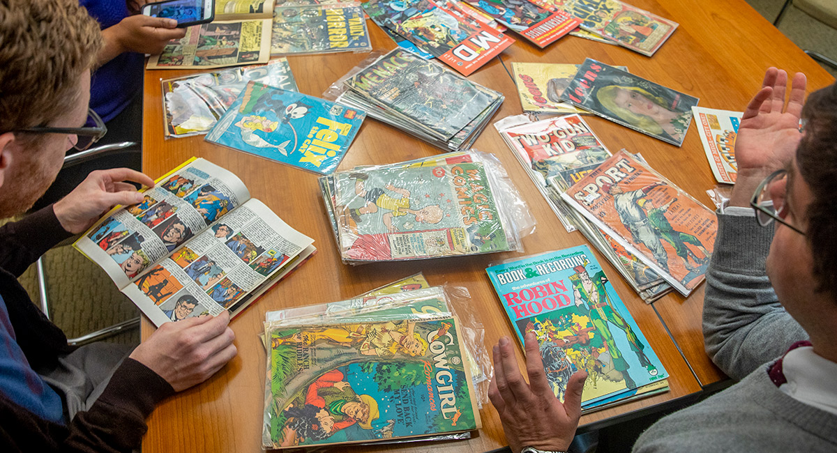 people gathered around a table full of comic books