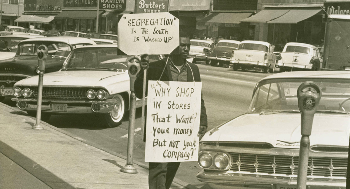 A man, possibly Gene Hawkins with 2 protest signs walking down Main Street, in which is  lined with cars. The two protest signs read: Segregation in the south is washed up and Why shop in stores that want your money but not your company? Many business and signs can be seen in the background.