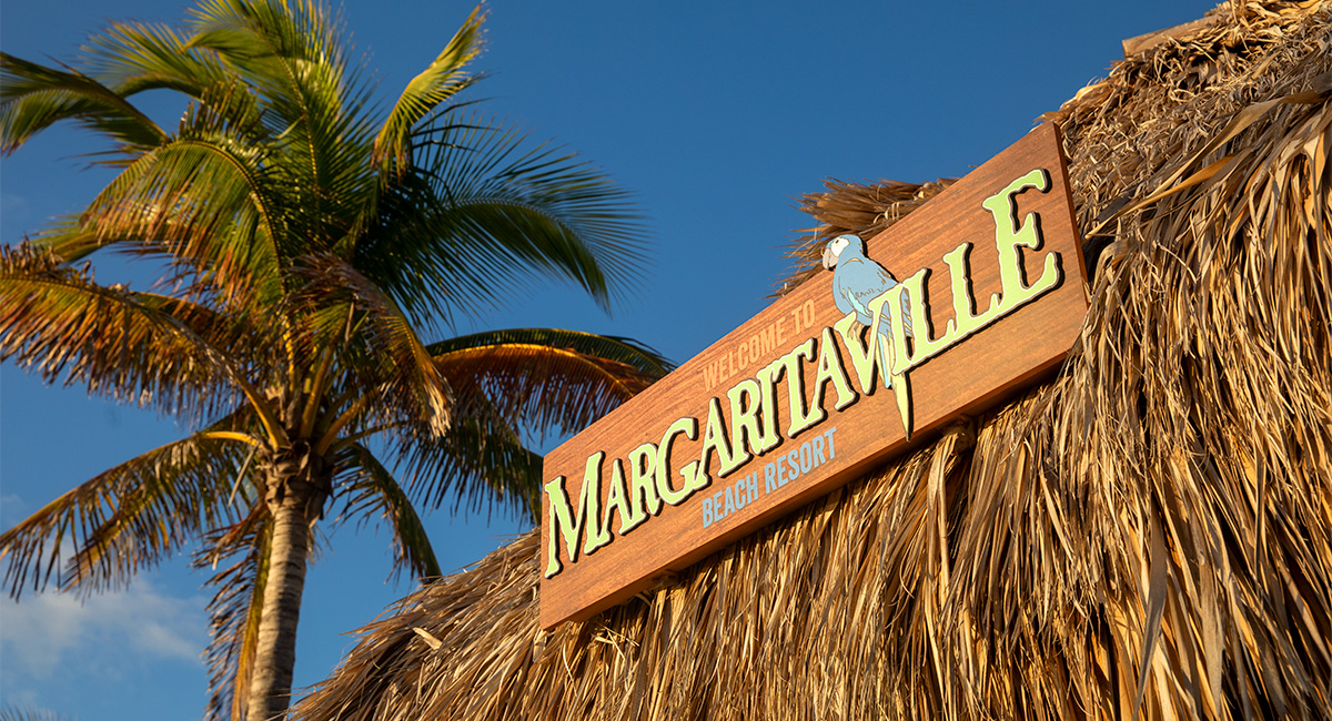 Margaritaville sign surrounded by blue skies and palm trees
