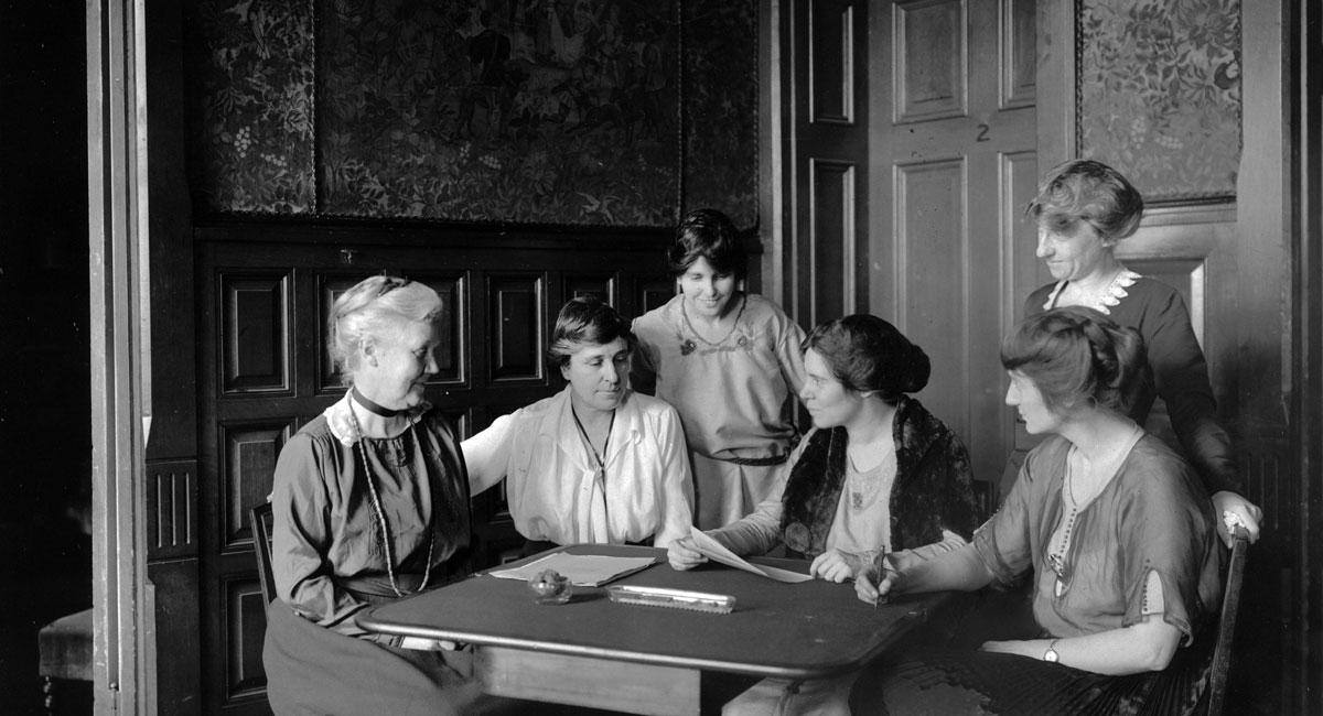 Conferring over ratification [of the 19th Amendment to the U.S. Constitution] at [National Woman's Party] headquarters, Jackson Pl[ace] [Washington, D.C.] 1919. L-R Mrs. Lawrence Lewis, Mrs. Abby Scott Baker, Anita Pollitzer, Alice Paul, Florence Boeckel, Mabel Vernon (standing, right)