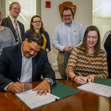 Megan Brown sits at a table with a man as they sign documents while others watch