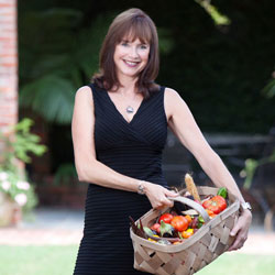 Patricia Moore-Pastides holding a basket of fresh produce