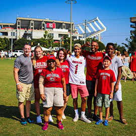 A large Gamecock family smiles at the photographer while standing against the background of Williams-Brice Stadium in the distance