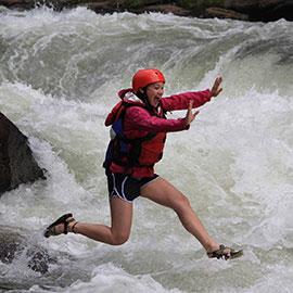 trips leader Ashley Hamada leaps through whitewater