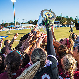 women's soccer celebrating with the SEC championship trophy