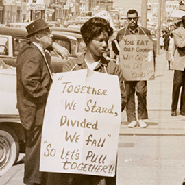 Two people with signs around their necks protesting segregation