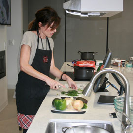 Cooking class instructor, Lindsay Shazly, dicing cilantro in a demonstration kitchen