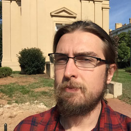 Ryan Waldman stands in front of Melton Observatory