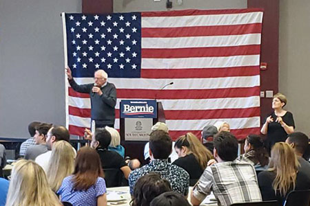 Senator Bernie Sanders addresses a crowd in the Russell House ballroom, stnading in front of a large American flag mounted on the wall.